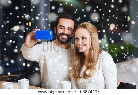 people, leisure, communication, technology and season - happy couple with smartphone taking selfie at winter cafe