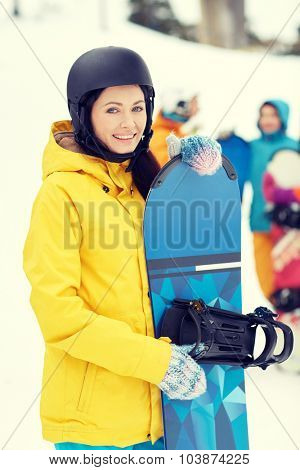 winter, leisure, extreme sport, friendship and people concept - happy young woman in helmet with snowboard and group of friends