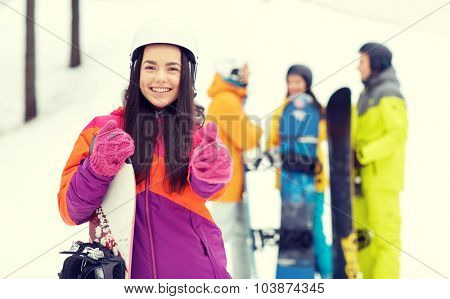 winter, leisure, extreme sport, friendship and people concept - happy young woman in helmet with snowboard and group of friends showing thumbs up