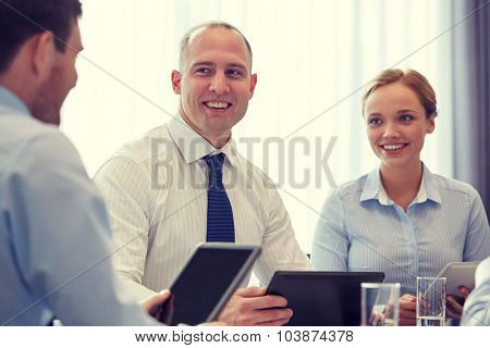business, conference, people, technology and teamwork concept - smiling businessmen and businesswoman with tablet pc computer meeting in office