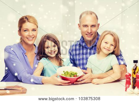 food, family, children, happiness and people concept - happy family with two kids showing salad in bowl at home