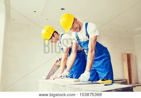 business, building, teamwork and people concept - group of smiling builders in hardhats with tools indoors