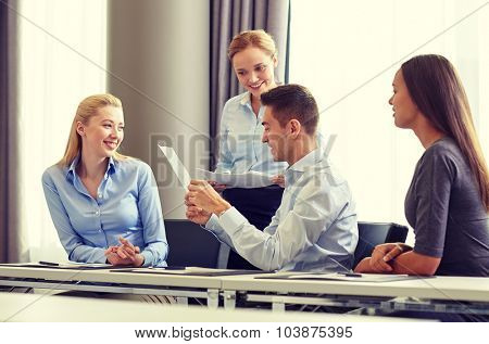 business, people and teamwork concept - smiling business team with papers meeting in office