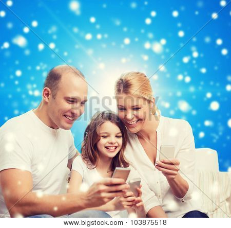 family, christmas holidays, technology and people concept - smiling mother, father and little girl with smartphones over blue snowy background
