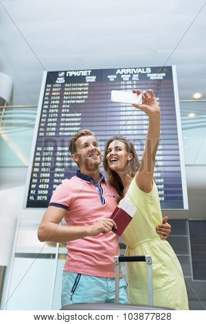Happy couple at the airport makes selfie