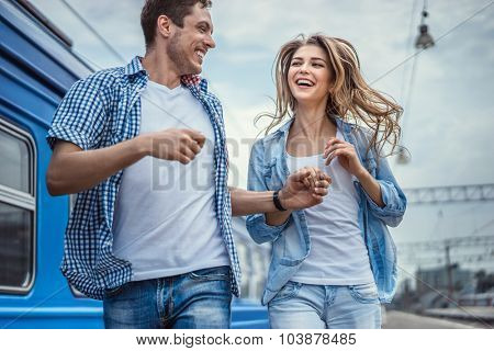 Happy running couple in a train station
