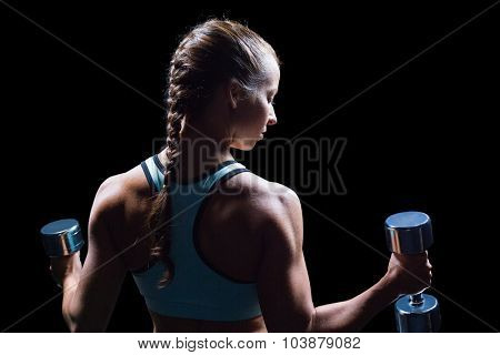 Rear view of woman exercising with dumbbells against black background