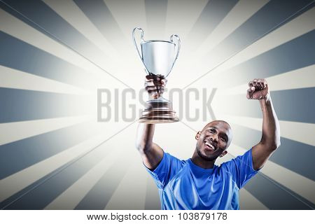 Happy sportsman looking up and cheering while holding trophy against linear background