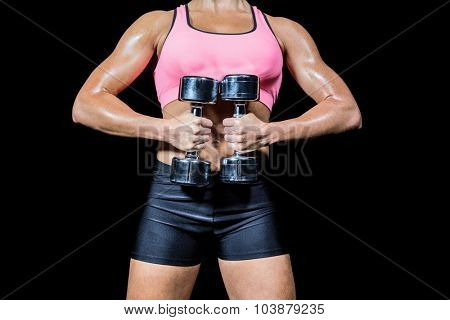 Midsection of woman doing workout with dumbbells against black background