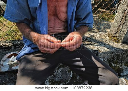 rolling by hands of cigarette without filter with tobacco cultivated on Lake Skadar near the border with Albania, Montenegro