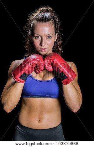 Portrait of pretty woman with fighting stance against black background