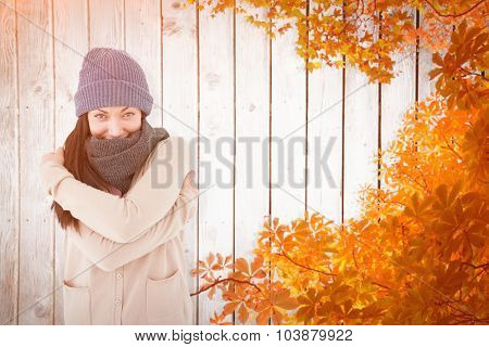 Attractive brunette looking at camera wearing warm clothes against autumn leaves on wood