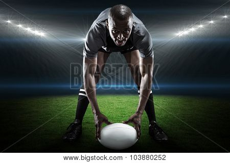Portrait of sportsman holding ball while playing rugby against rugby stadium