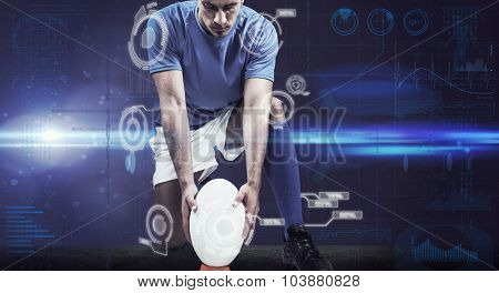 Full length of rugby player placing ball against fitness interface