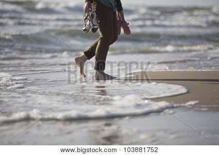 Woman's Legs Walking By Sea Shore