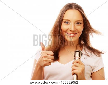 Happy singing girl. Beauty woman wearing white t-shirt  with microphone over white background.