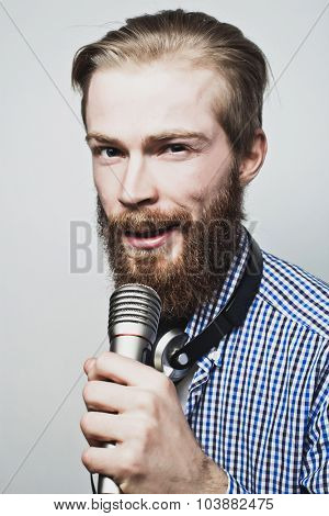 Life style concept: a young man with a beard wearing a white shirt holding a microphone and singing. Over gray background.