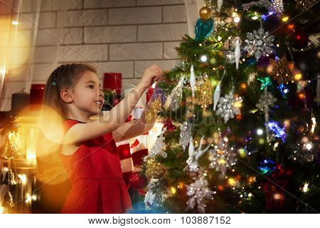 Girl is decorating the Christmas tree