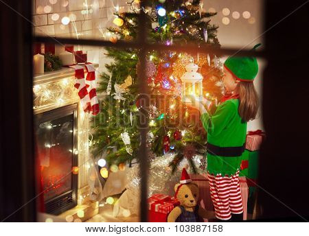 Little girl in costume of Christmas elf standing with a lantern in her hand by the Christmas tree