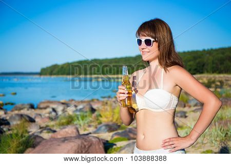 Beautiful Woman In Bikini With Beer Posing On The Beach