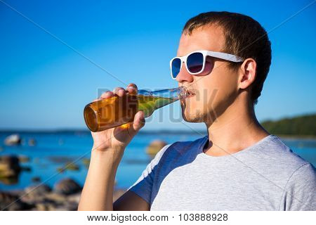 Summer Concept - Handsome Man Drinking Beer On The Beach