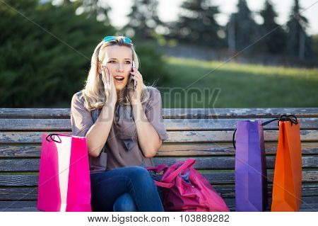 Young Surprised Woman Sitting On A Bench After Shopping