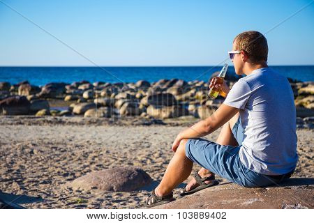 Back View Of Man Drinking Beer On Stony Beach