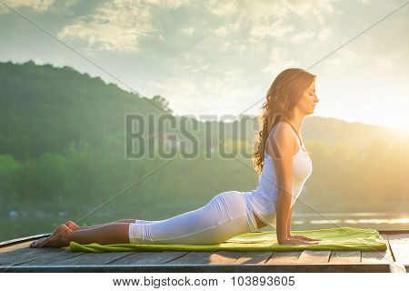 Woman doing yoga on the lake - relaxing in nature
