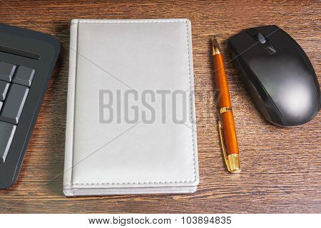 Composition With Planner,  Mouse, Pen And Keyboard Laying On Wooden Desk