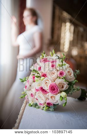 Bride in window frame and wedding bouquet in the foreground. Wedding bouquet with a bride