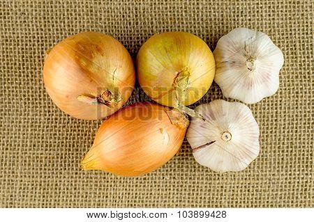 Overhead Macro Of Garlic And Onion Root Veggies On Hessian Material