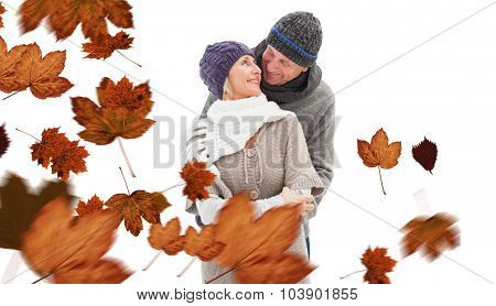 Happy mature couple in winter clothes embracing against autumn leaves