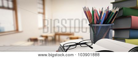 School supplies on desk against empty classroom