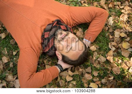 Handsome middle-aged man lying on the autumn leaves in park