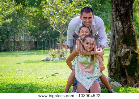 Young Father With Two Daughters In A Park In Summer