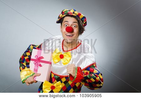 Clown with giftbox in funny concept