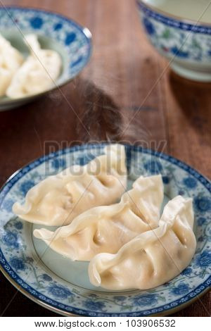 Fresh dumpling on plate. Chinese cuisine on rustic vintage wooden background. Fractal on the plate is generic print.