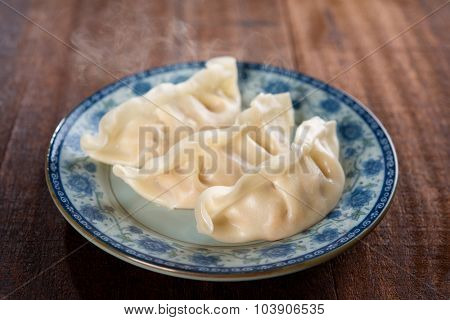 Fresh dumpling on plate. Chinese cuisine with hot steams on rustic vintage wooden background. Fractal on the plate is generic print.