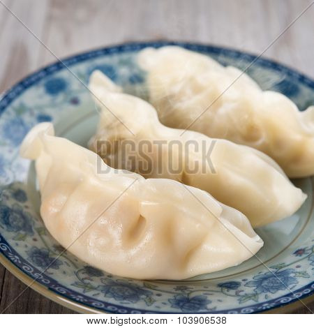 Close up fresh dumpling on plate. Chinese cuisine on old wooden background. Fractal on the plate is generic print.