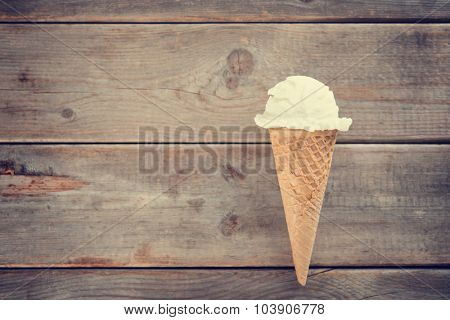 Single vanilla ice cream in a waffle cones over wooden background with copy space.  Vintage toned.