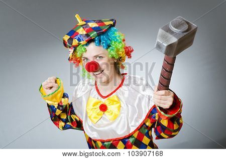 Clown with hammer in funny concept
