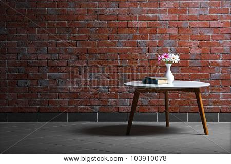 Table with flowers and books on brick wall background