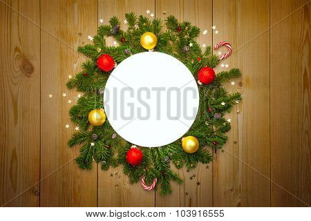 Christmas Round Frame with firtree, candies and baubles with stars on rustic wood, copy space for text