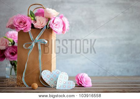 Love background with pink roses flowers, bow and paper handmade hearts