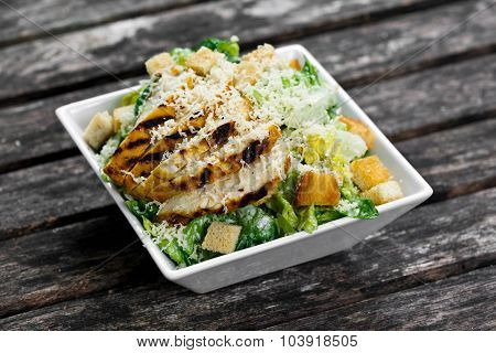 Caesar Salad With Chicken And Lettuce On Wooden Table