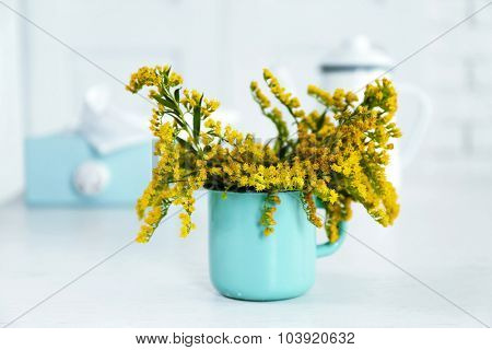 Beautiful flowers in decorative vase on table, on light background
