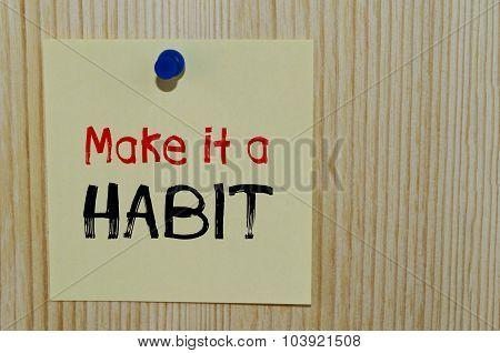Make it a habit written on yellow paper note