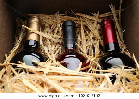 Three wine bottles in box with straw
