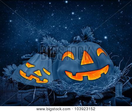 Halloween night background, funny carved pumpkins head glowing in dark starry night, traditional decoration for october holiday