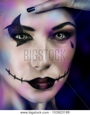 Closeup portrait of woman with makeup for Halloween party over dark blue background,  terrifying witch, dead zombie look